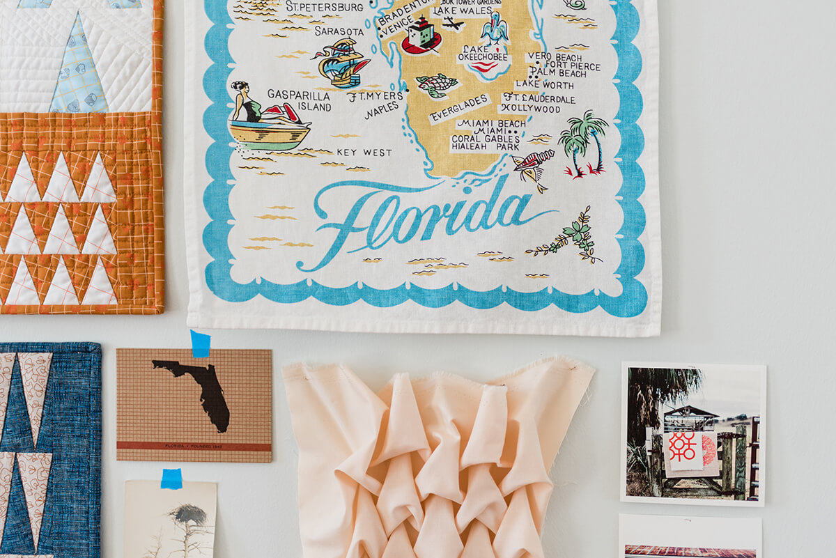 wall collage with mini quilts, Florida tea towel, postcards and pictures