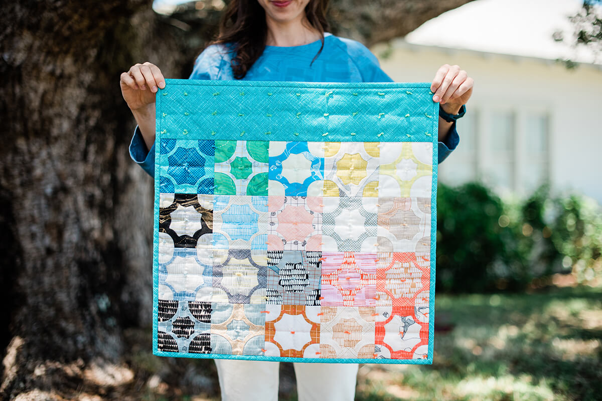 Carolyn holding a small, colorful Everglade quilt under a tree