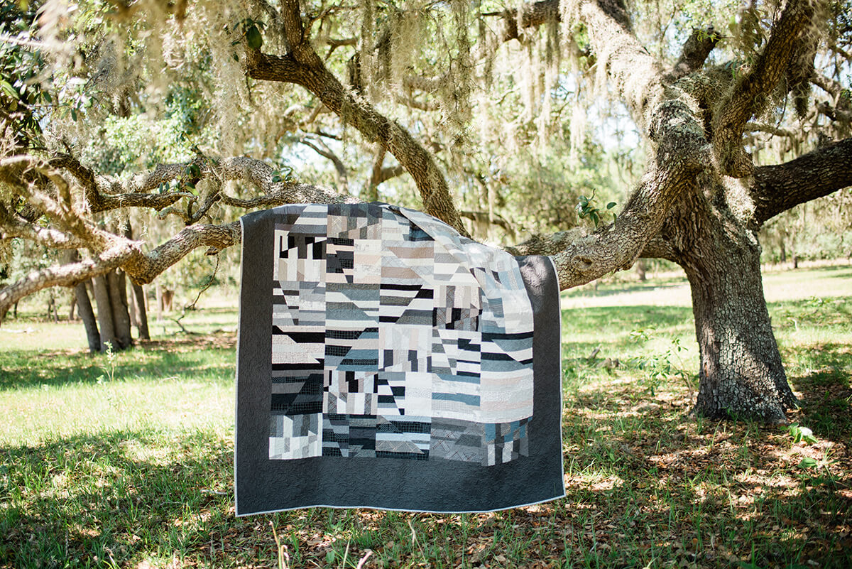 Greyscale Aerial quilt draped on a live oak with Spanish moss and dappled sunlight